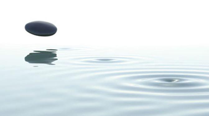 zen stone thrown on the water on white background
